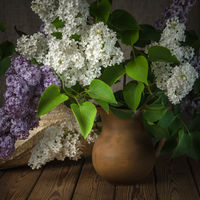 Still-life with a bouquet of lilacs and a straw hat