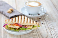 Grilled chicken sandwich with a coffee