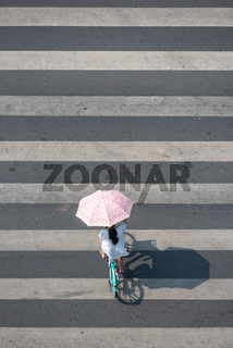 Young chinese woman with an umbrella walking on a zebra crossing