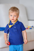 Two year old boy playing doctor