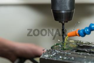 Mit Bohrmaschine und mithilfe eines Kühlmittels in Kunststoff Löcher bohren - Nahaufnahme