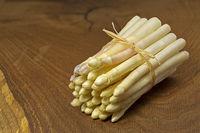 Bund frischer weißer Spargel auf Holzbrettchen