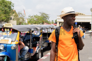 Happy black African tourist man in Bangkok with tuk tuk taxis
