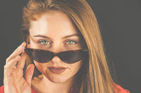 Woman, 23-30 years young, brunette, portrait with sunglasses against dark background.