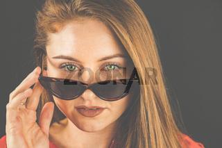 Frau, 23-30 Jahre jung, brünett, Portrait mit Sonnenbrille vor dunklem Hintergrund.