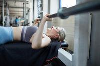 Frau beim Bankdrücken im Fitnesscenter