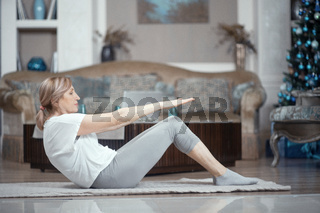 Adult Woman Over 50 Years Old Doing Yoga at Home in the Living Room.