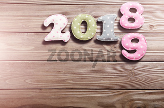 Colorful stitched digits 2 0 1 8 9 made of polkadot fabric flat lyed on wooden background