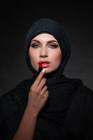 Portrait of arab woman painting her lips