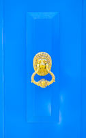blue wooden door with lion´s head and door knocker