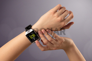 Female hand wearing and pressing smartwatch