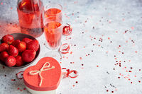Bottle of rose champagne, glasses with fresh strawberries and heart shaped gift