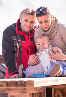 young happy family with little child enjoying winter day