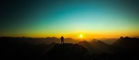 Man reaching summit enjoying freedom and looking towards mountains sunrise.