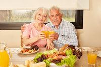 Paar Senioren beim Anstoßen mit Orangensaft