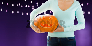 close up of woman holding halloween pumpkin