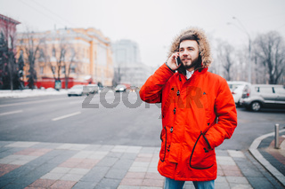 young guy with beard and red jacket in hood a student uses mobile phone, holds in his hand near the head, talking on the phone with smile on the background of red building the university or college