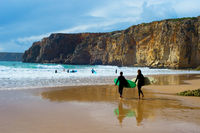 Surfers surfboards beach Portugal cliff