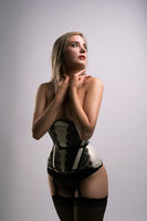 Young blonde in sexy corset and stockings shot