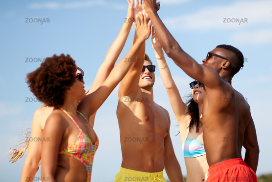happy friends making high five on summer beach