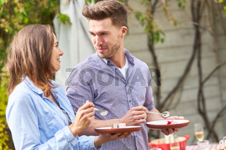 Junges Paar beim Kuchen essen auf einer Gartenparty