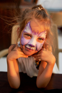 Pretty exciting blue-eyed girl of 5 years with a face painting