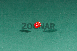 One red dice falling on a green table