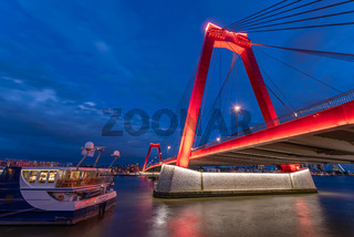 Red cable bridge against cloudy sky at night