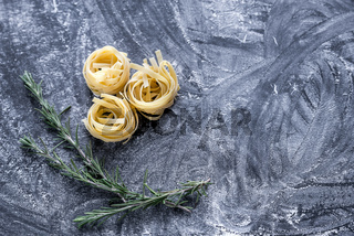 Raw tagliatelle nido on the flour-dusted black wooden background