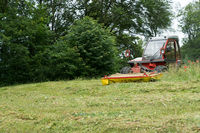 small tractor with mower in front cutting a steep hillside wildflower meadow in the Alps for hay