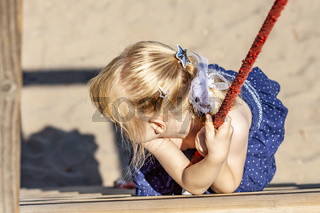 Young girl hanging on a swing at outdoor playground