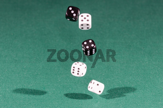 Four white and black dices falling on a green table