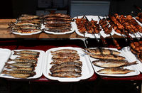 fish whole grilled and meat on skewers cooked entirely on an open fire lie on white trays on the embankment near the Black Sea. Reportage shooting. Republic of Crimea