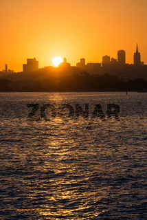 The sunrise sun rising over downtown San Francisco, California, USA from the Torpedo Wharf