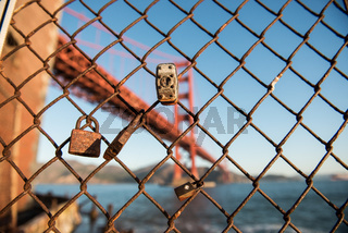 Padlocks on a fence and the Golden Gate Bridge in the background at Fort Point, San Francisco, California, USA