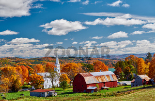 Church and farm with red barn at autumn