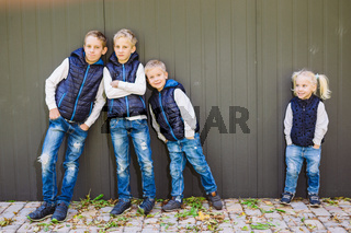Funny Caucasian big family of three brothers and sister posing standing on growth background of wall in full growth. Equally stylishly dressed in blue vests and jeans. Theme girl in male circle