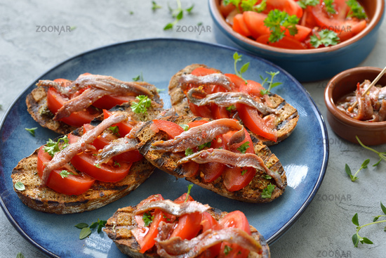 Grilled slices of bread with tomatoes and anchovy fillets