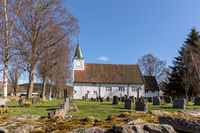 Sogne, Norway - April 21, 2018: Old Sogne Church. White wooden church in Sogne, a parish church in Sogne, Vest-Agder in Norway. Blue sky, green grass.