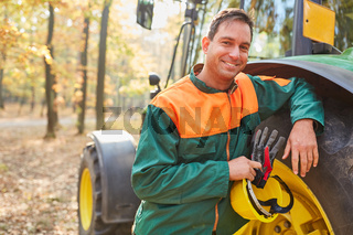 Zufriedener Waldarbeiter lehnt am Forwarder