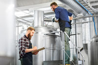 men with clipboard at brewery kettle or beer plant