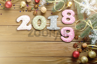 Colorful stitched digits 2 0 1 8 9 of polkadot fabric with Christmas decorations flat lyed on wooden background. Place for text