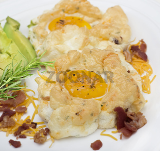 Cloud eggs and avocado on a white plate