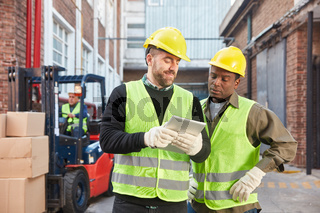 Zwei Logistik Arbeiter mit Tablet PC