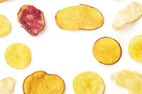 Dried fruit and vegetable chips, healthy vegan snack, top shot on a white background, forming a frame with a place for text