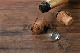 Open bottle of champagne with corks on a wood table with copy space