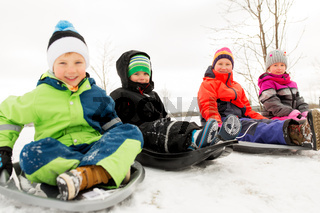 happy little kids sliding on sleds in winter