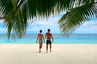 Beautiful Maldives beach with tourist couple