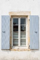 Old window with wooden gray painted shutters