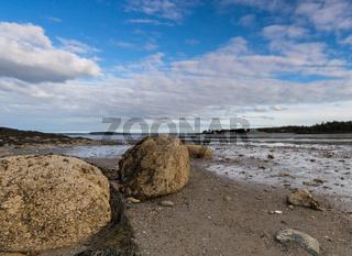 coastal landscape at low tide with large rocks under a blue sky in Fundy Bay